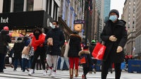 People wear face masks as they walk through Herald Square in New York City in January 2021. Getty Images.