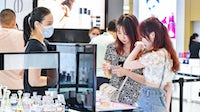 Customers shop for perfumes at Haikou Riyue Plaza Duty Free Shop. Getty Images.