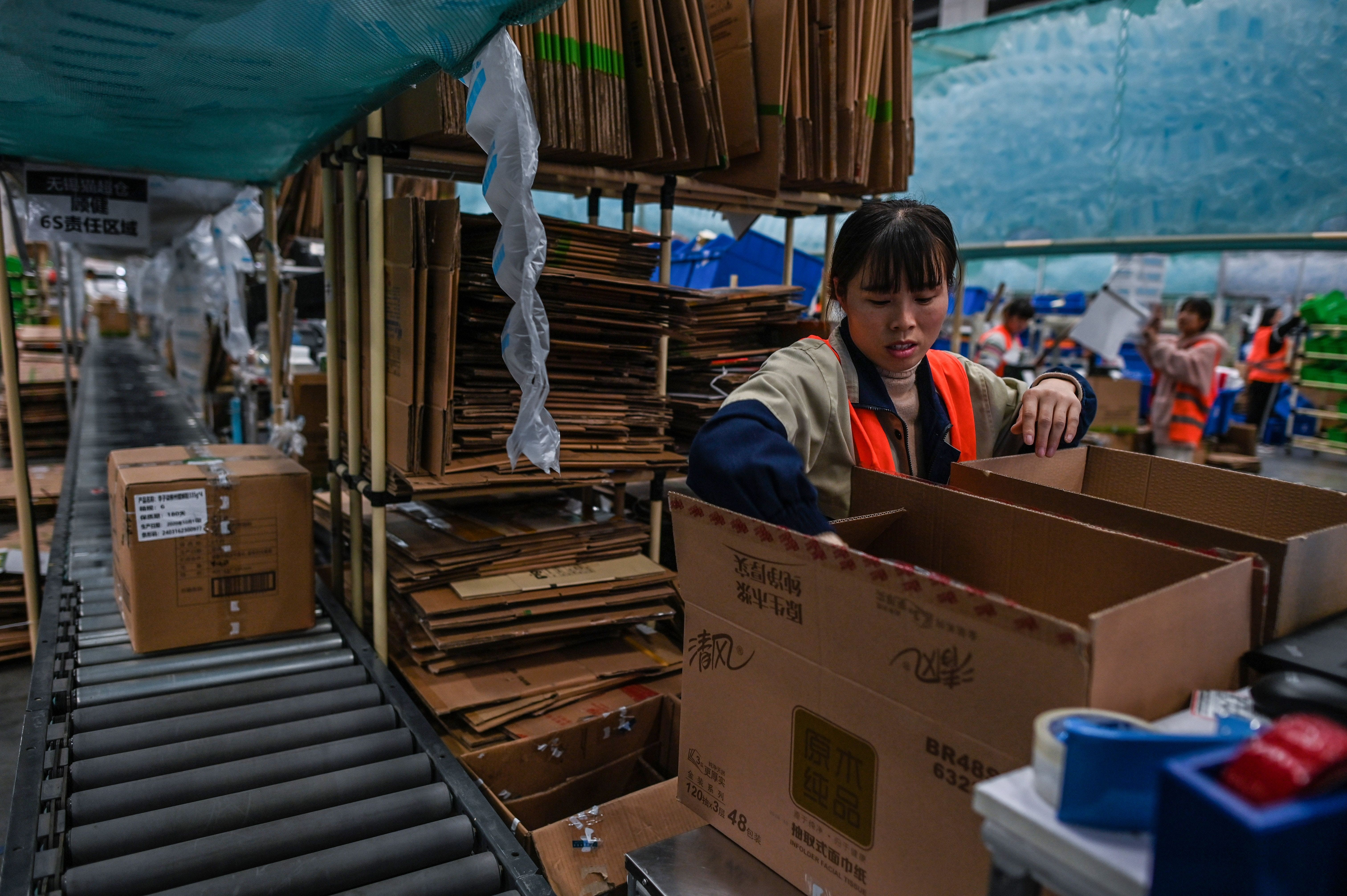 Employees pack boxes in a Cainiao warehouse  in Wuxi, China\'s eastern Jiangsu province, ahead of Singles\' Day 2020. Getty Images.