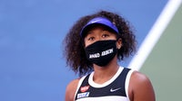 Naomi Osaka wears a protective face mask with the name of Ahmaud Arbery — a Black man fatally shot by a group of white men while jogging  —  at the 2020 US Open.