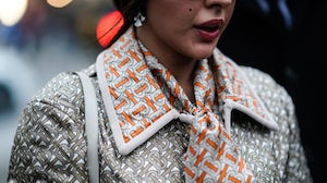 A guest wears a Burberry jacket and monogram scarf at London Fashion Week. Edward Berthelot for Getty Images.