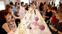 Customers try out products at a Glossier pop-up. Getty Images.