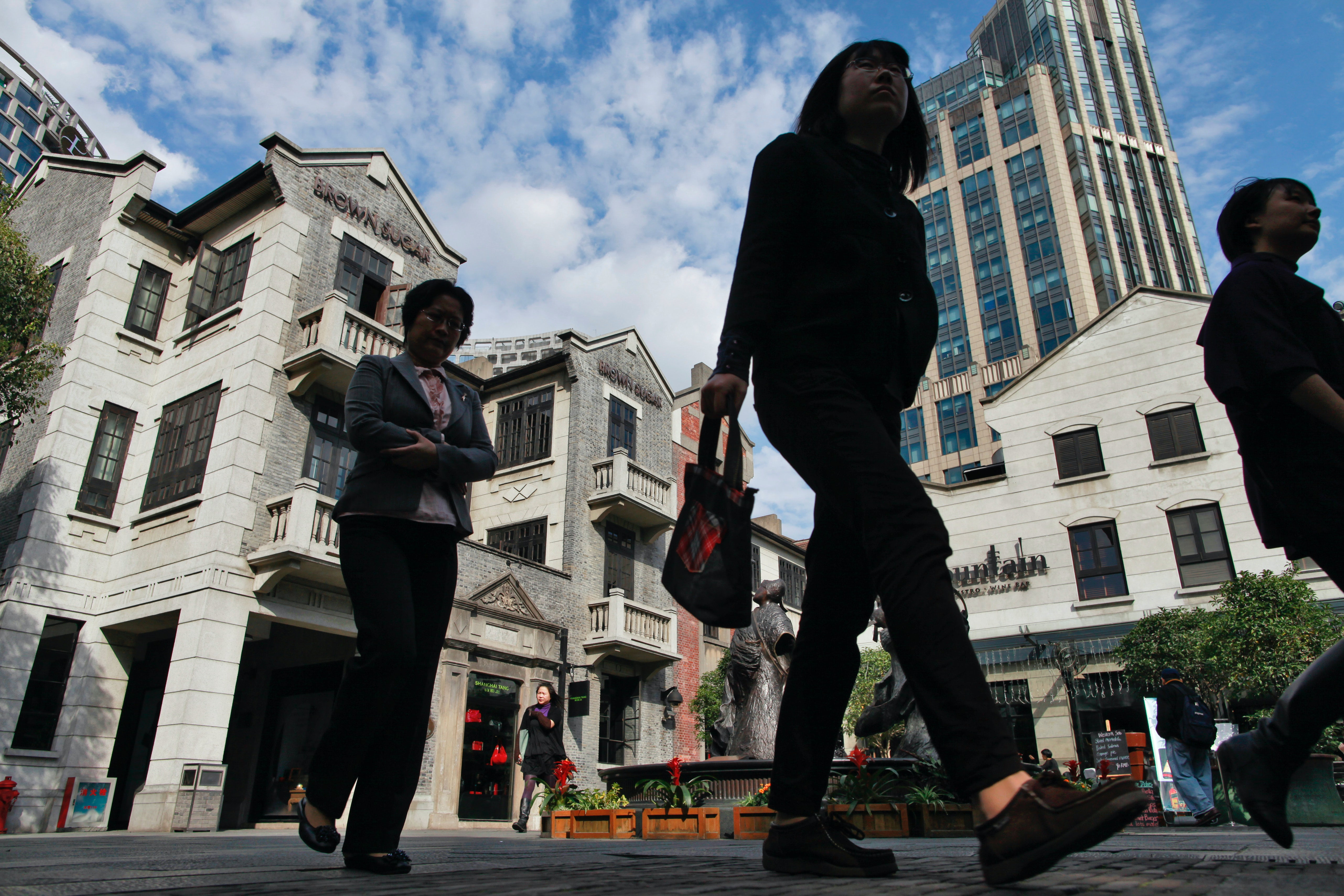 Visitors and shoppers walk through Shui On Group's mall in Shanghai, China. Getty Images.