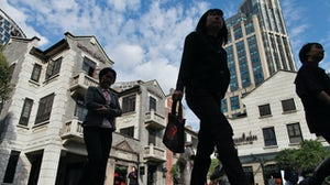 Visitors and shoppers walk through Shui On Group's in Shanghai, China. Getty Images.