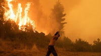 A resident shields himself from the heat of a forest wildfire in Pefki on Evia island, Greece, on August 8, 2021. Getty Images.