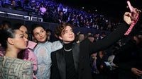 VIP guests including model Sasha Meneghel and singer João Figueiredo pose for a selfie at Balmain's festival during Paris Fashion Week. Getty Images.