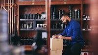 Salesman kneeling while writing on paper. Maskot via Getty Images.