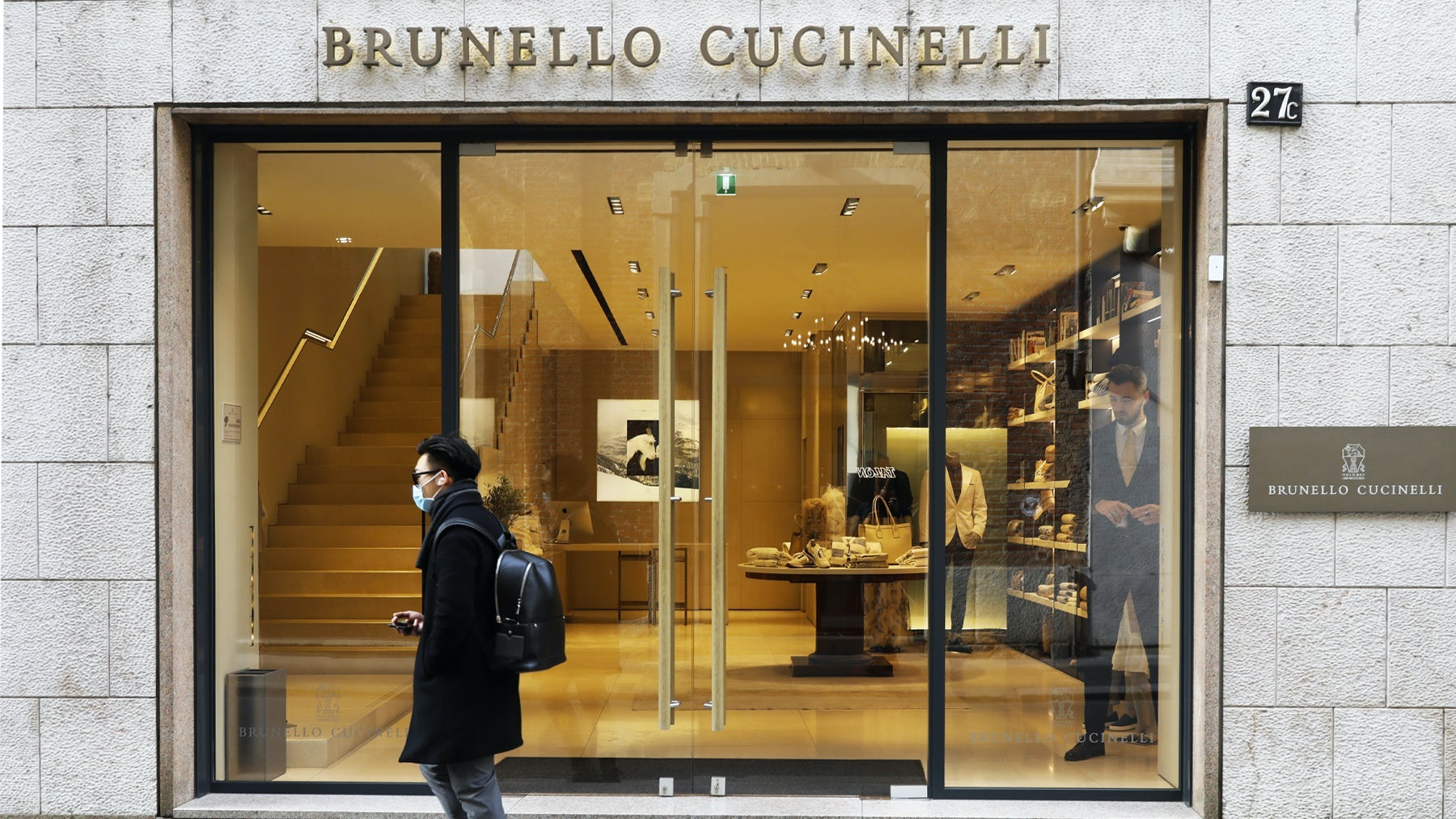 A man wears a protective mask as he walks in front of the Brunello Cucinelli store on via Montenapoleone in Milan. Getty Images.