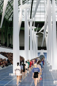 Models walk a Chanel catwalk paved with solar panels and framed by wind turbines. The fashion industry will need to invest billions in changes like a shift to renewable energy to meet its climate goals. Getty Images.