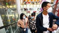 购物者在10月2日,2021年10月2日,在中国的黄金周假期骑自动扶梯。
