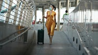 A woman walking with luggage at a railroad station. Getty Images.