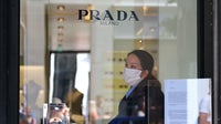 A staff member of Prada, wearing a mask and protective plastic gloves, stands behind a glass door with an advisory on how to shop amid coronavirus. Getty Images.