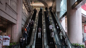 People wearing protective masks ride on escalators at the Times Square shopping mall, operated by Wharf Holdings Ltd., in the Causeway Bay district of Hong Kong in February, 2020. Getty Images.
