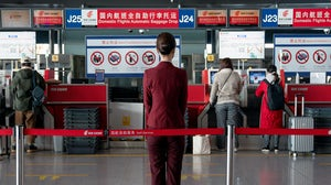A staff stands in front of Air China Ltd. baggage drop counters for domestic flights at Beijing Capital International Airport ahead of Lunar New Year. Yan Cong/Bloomberg via Getty Images.