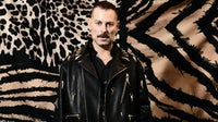 """Fausto Puglisi poses in front of the """"United States of Cavalli"""" flag. Roberto Cavalli."""