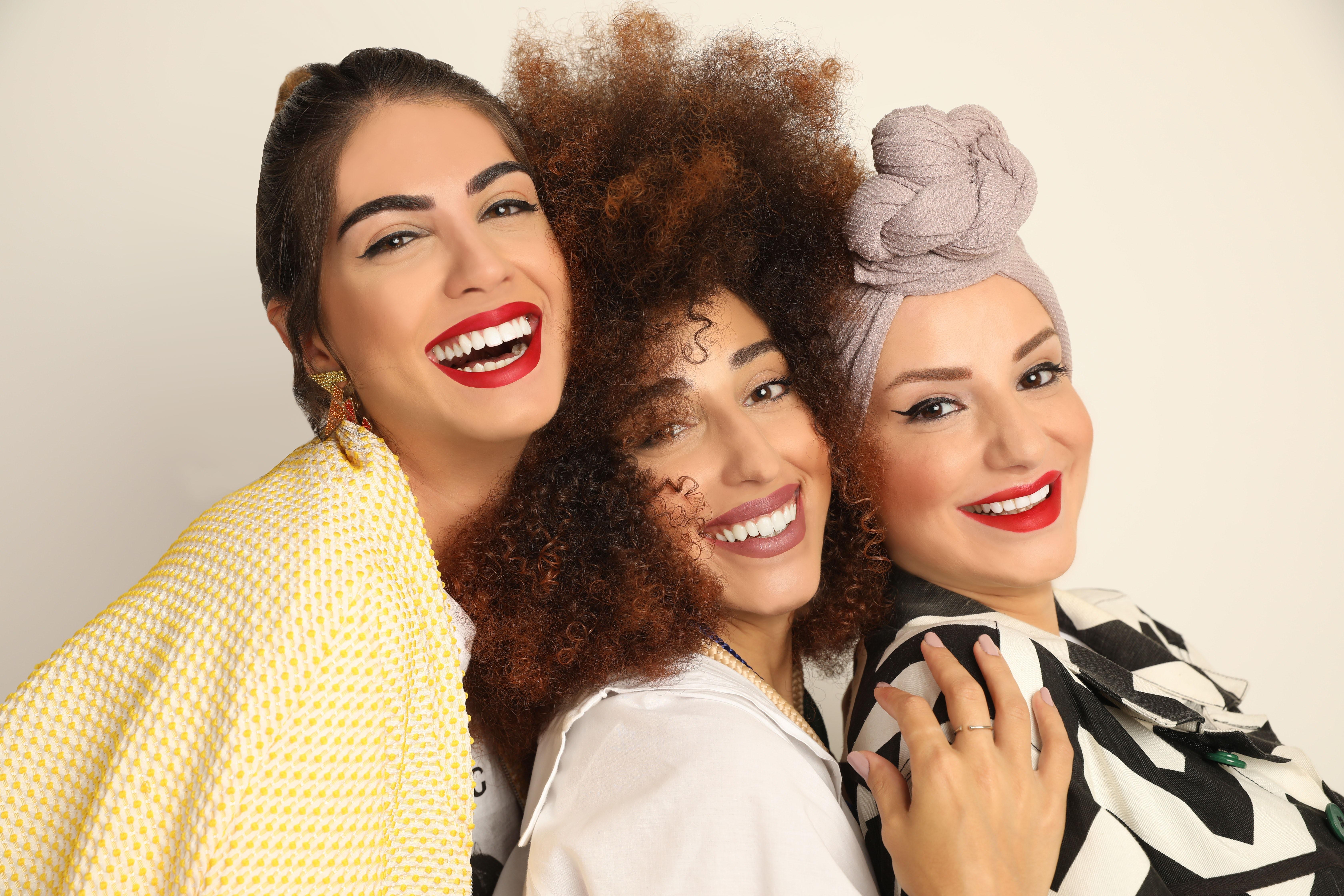 Models sporting Shade M Beauty\'s matte liquid lipstick. Shade M.