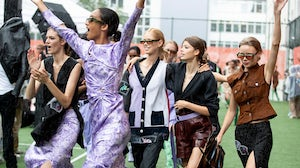 Models dancing in the rain at the Ganni Spring/Summer 2020 show in Copenhagen. Getty Images.