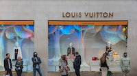 Masked shoppers queuing outside the Louis Vuitton store In London's Bond Street. Getty Images.