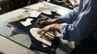 Craftsperson working in an Italian shoe factory. Shutterstock.