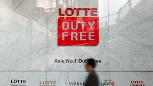 A man walks past signage for a Hotel Lotte Co. Duty Free store in Seoul, South Korea. Getty Images.