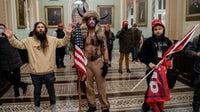 Supporters of US President Donald Trump, including Jake Angeli, a QAnon supporter known for his painted face and horned hat, enter the US Capitol. Getty Images.