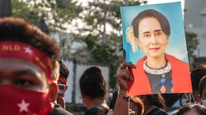 A supporter of Myanmar's National League for Democracy holds a portrait of politician Aung San Suu Kyi during a demonstration. Getty.