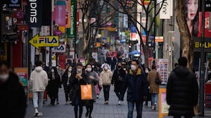 Pedestrians wearing face masks walk through Seoul's Myeongdong shopping district. Getty Images.