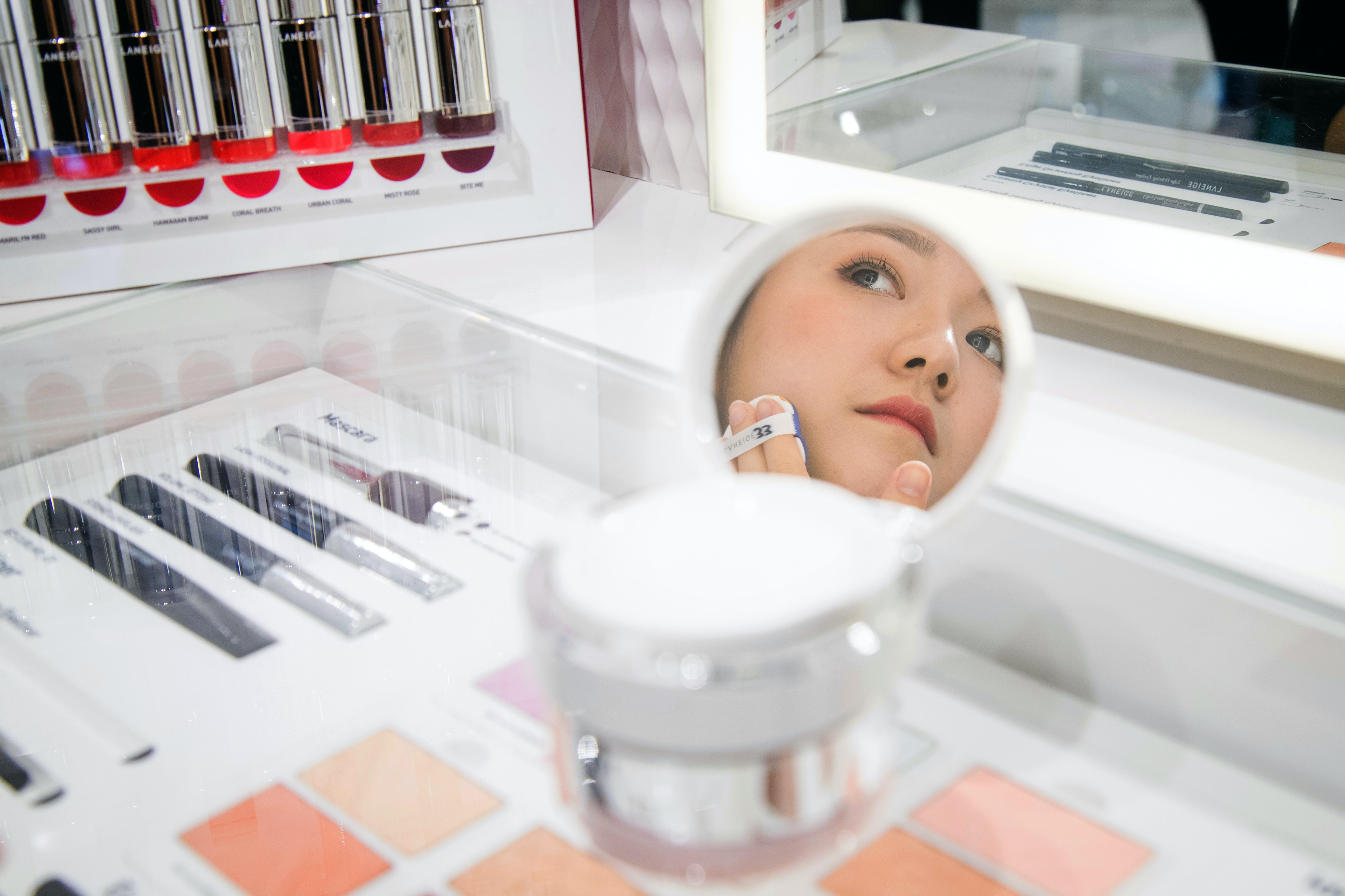 A store employee applying foundation in a Laneige boutique. Getty Images.