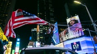 A boy with the United States flag stands in Times Square — prime advertising space for America's biggest brands — after it was announced that Democratic candidate Joe Biden would be the next president of the United States. Getty Images.