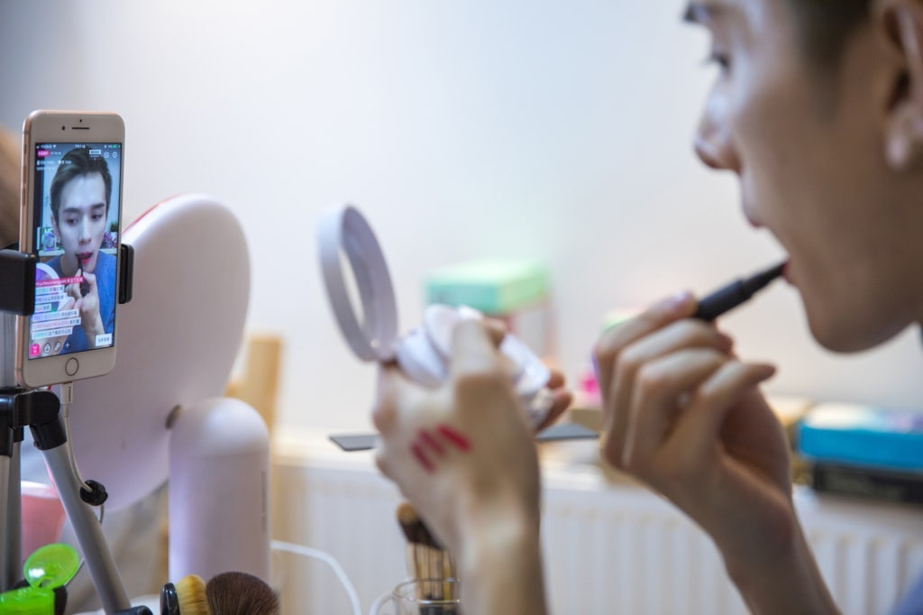 Beauty blogger Austin Li Jiaqi applies lipstick while livestreaming on the e-commerce platform Taobao. Getty Images.