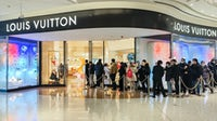 Customers wait in line to enter a Louis Vuitton shop in Shanghai. Getty Images.