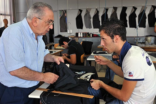 A teacher explains the art of tailoring to a student at the Brioni tailoring school in Italy