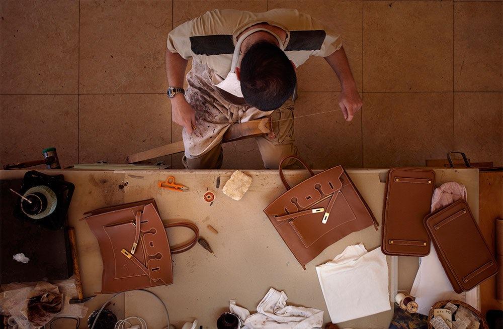 An artisan piecing together a leather handbag   Source: Hermès
