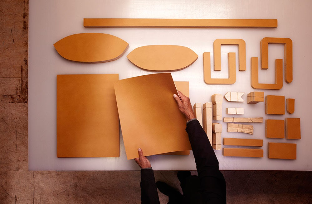 An artisan prepares leather pieces to be made into a handbag | Source: Courtesy Hermès