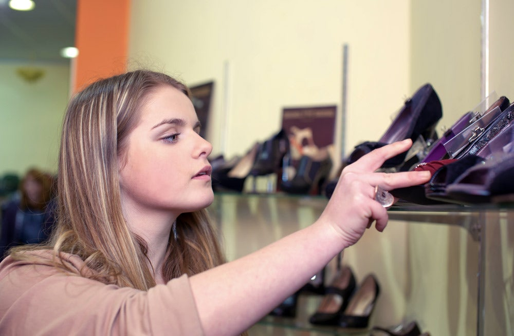 A young woman shopping for shoes | Source: Shutterstock