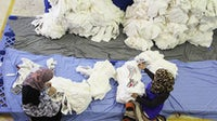 Jordanian garment workers quality-checking pieces of fabric | Photo: Ibraheem K. Shaheen