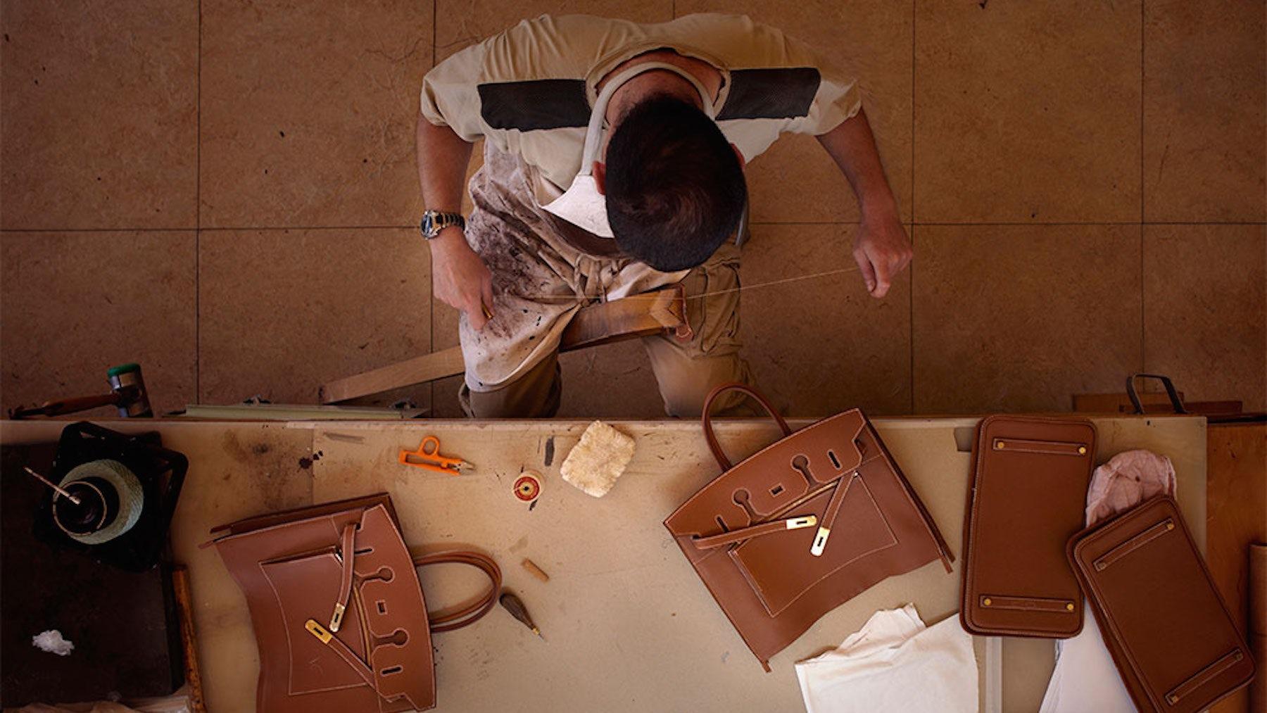 An artisan piecing together a leather handbag | Source: Hermès