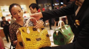 A Chinese consumer considers a Louis Vuitton bag | Source: Reuters