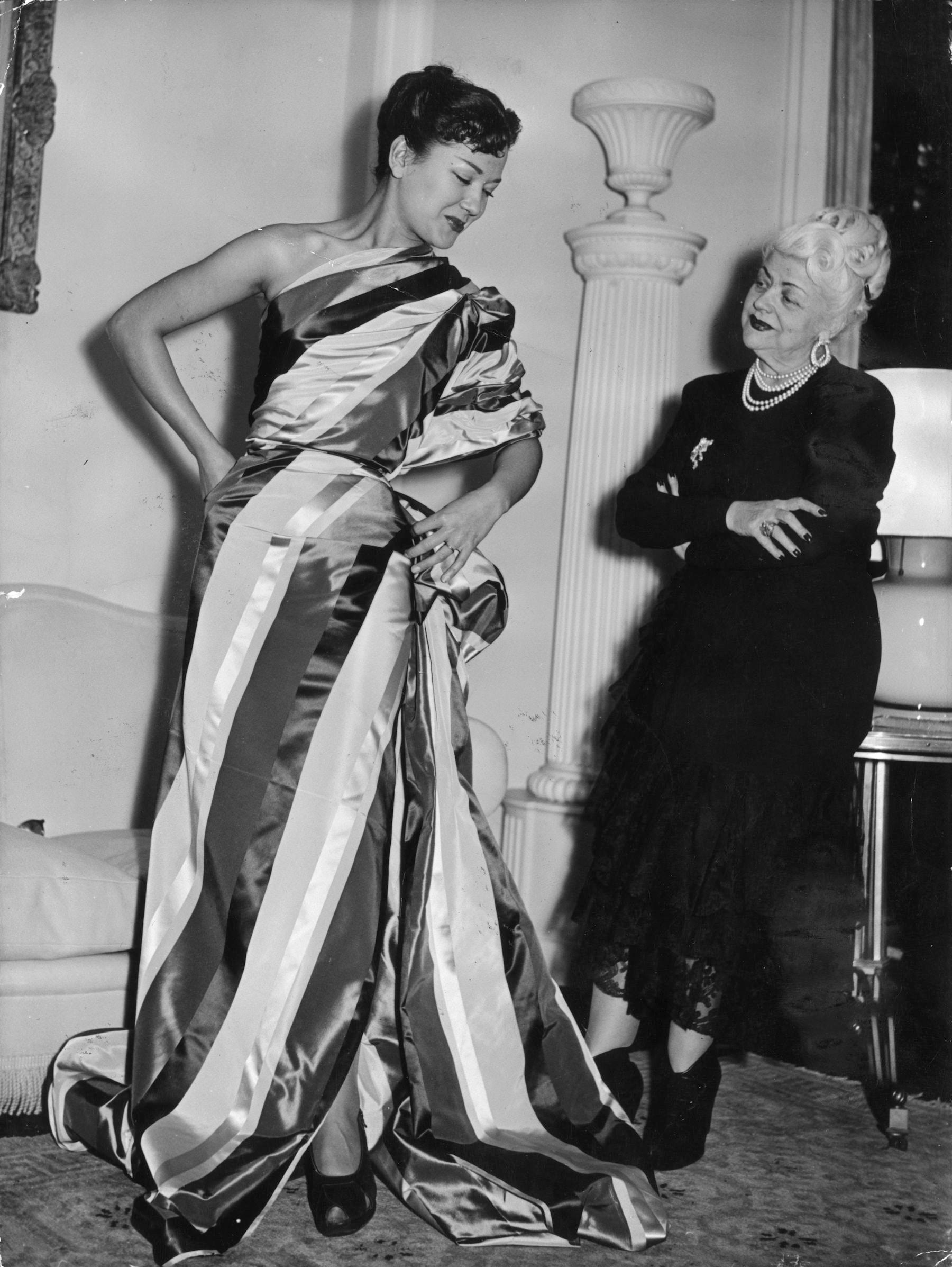 1948: Dress designer Madame Nina Ricci on the right, casting a critical eye at a mannequin whom she has draped with material to make an instant dress   Source: Getty