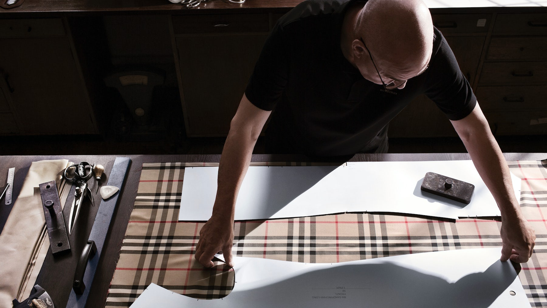 A craftsman cuts signature Burberry check fabric for a trench coat | Source: Courtesy