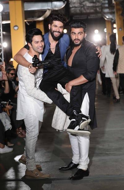 Varun Dhawan and Arjun Kapoor lift designer Kunal Rawal at Lakme Fashion Week in Mumbai | Source: Courtesy