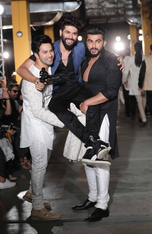 Varun Dhawan and Arjun Kapoor lift designer Kunal Rawal at Lakme Fashion Week in Mumbai | Source: Courtesy