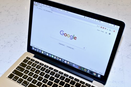 A laptop displays Google's search page