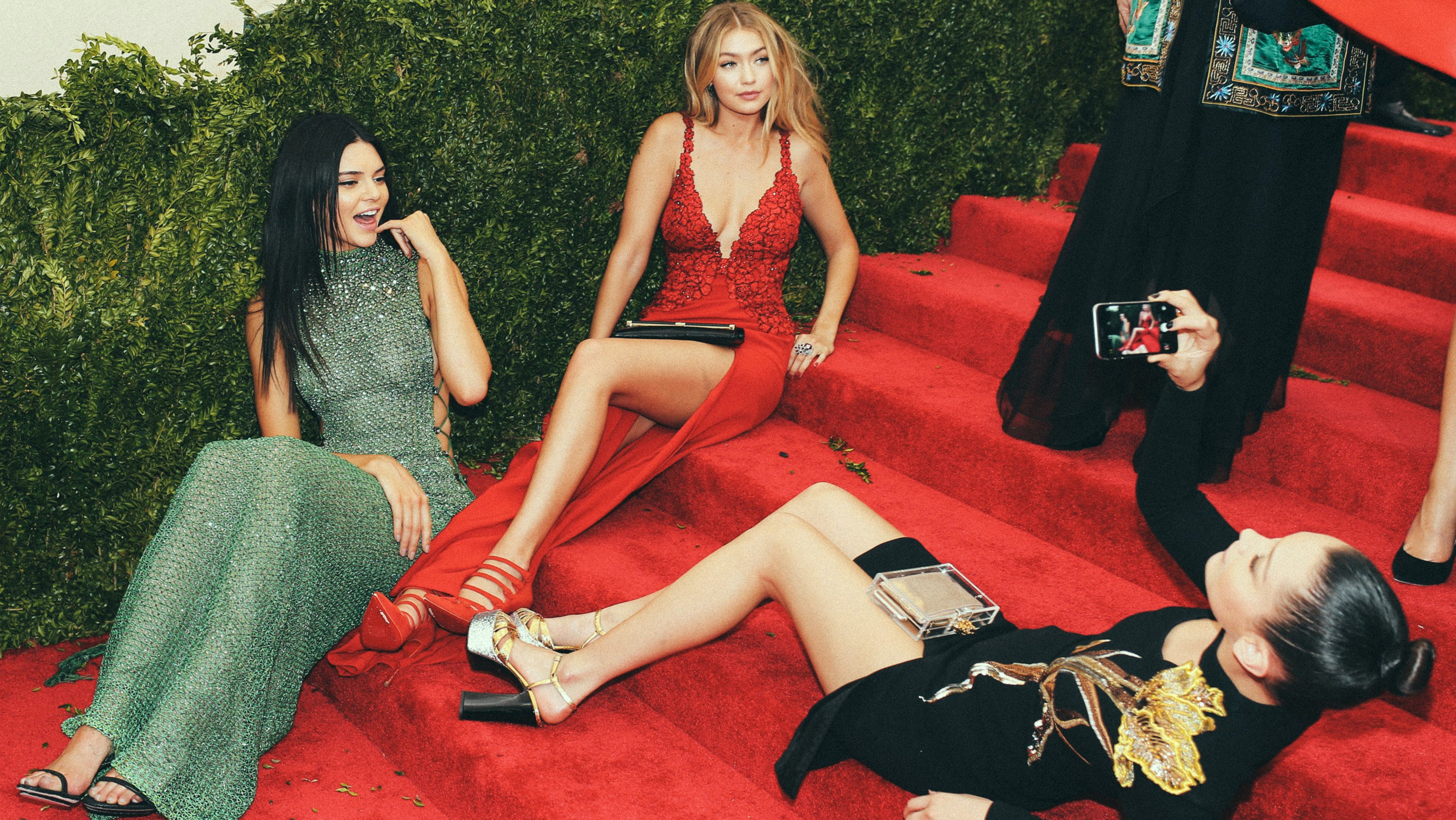 Bella Hadid takes a picture of Kendall Jenner and Gigi Hadid on her phone at the 2015 Met Gala | Source: Phil Oh