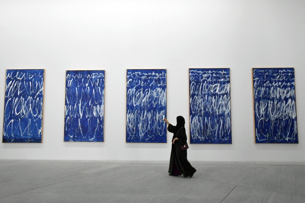 A visitor at an exhibition at the grand opening of the Louvre Abu Dhabi Museum in the United Arab Emirates