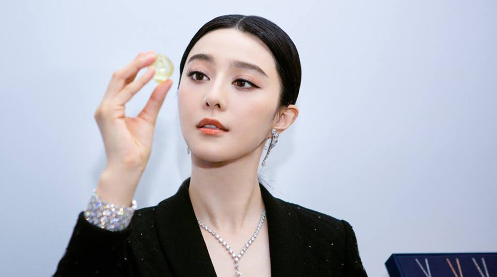 Fan Bingbing wearing De Beers' Phenomena Glacier bracelet, examining a diamond | Source: De Beers