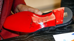 Christian Louboutin signs shoes | Source: Isa Foltin/Getty Images