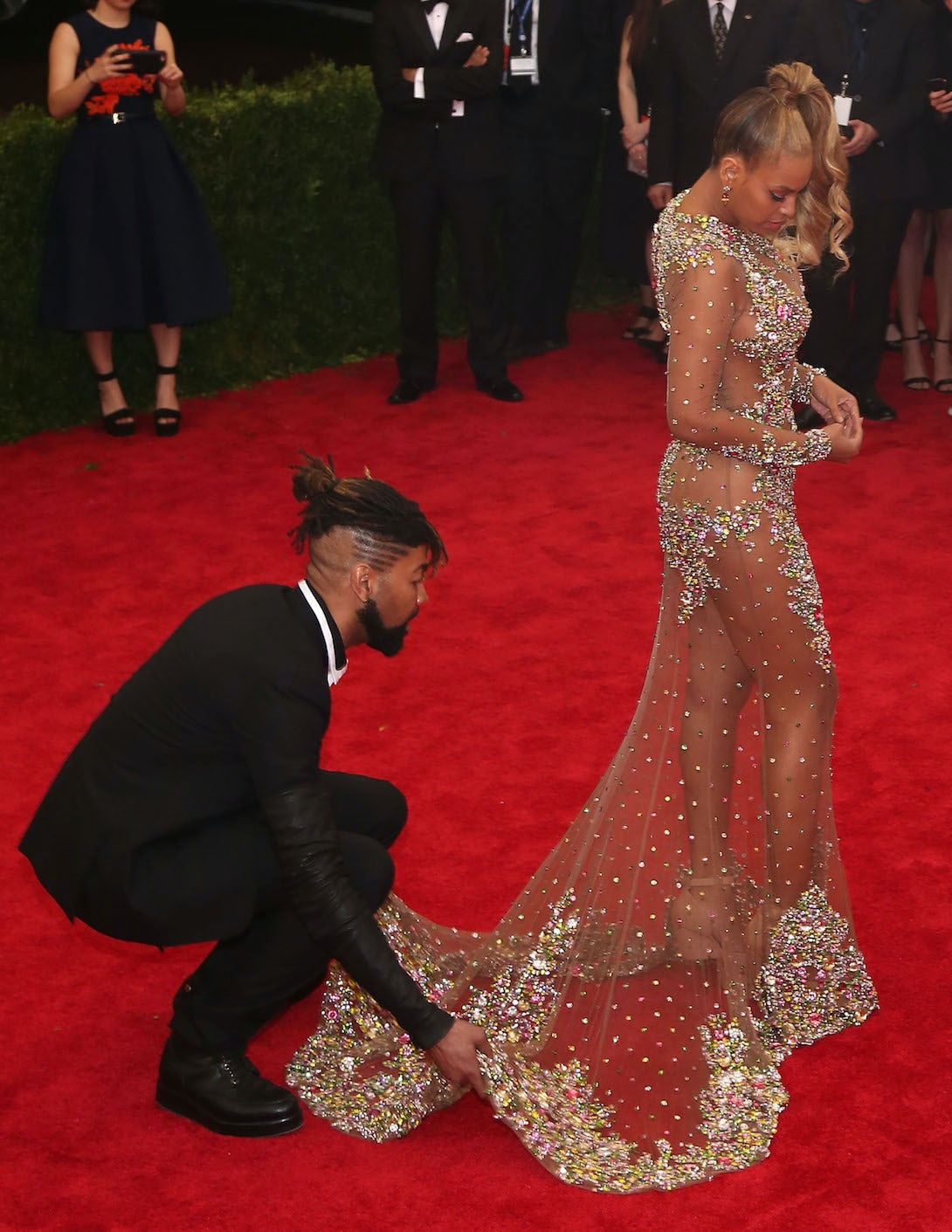 Celebrity stylist Ty Hunter attends to Beyoncé's dress at the Met Ball 2015 | Source: Getty