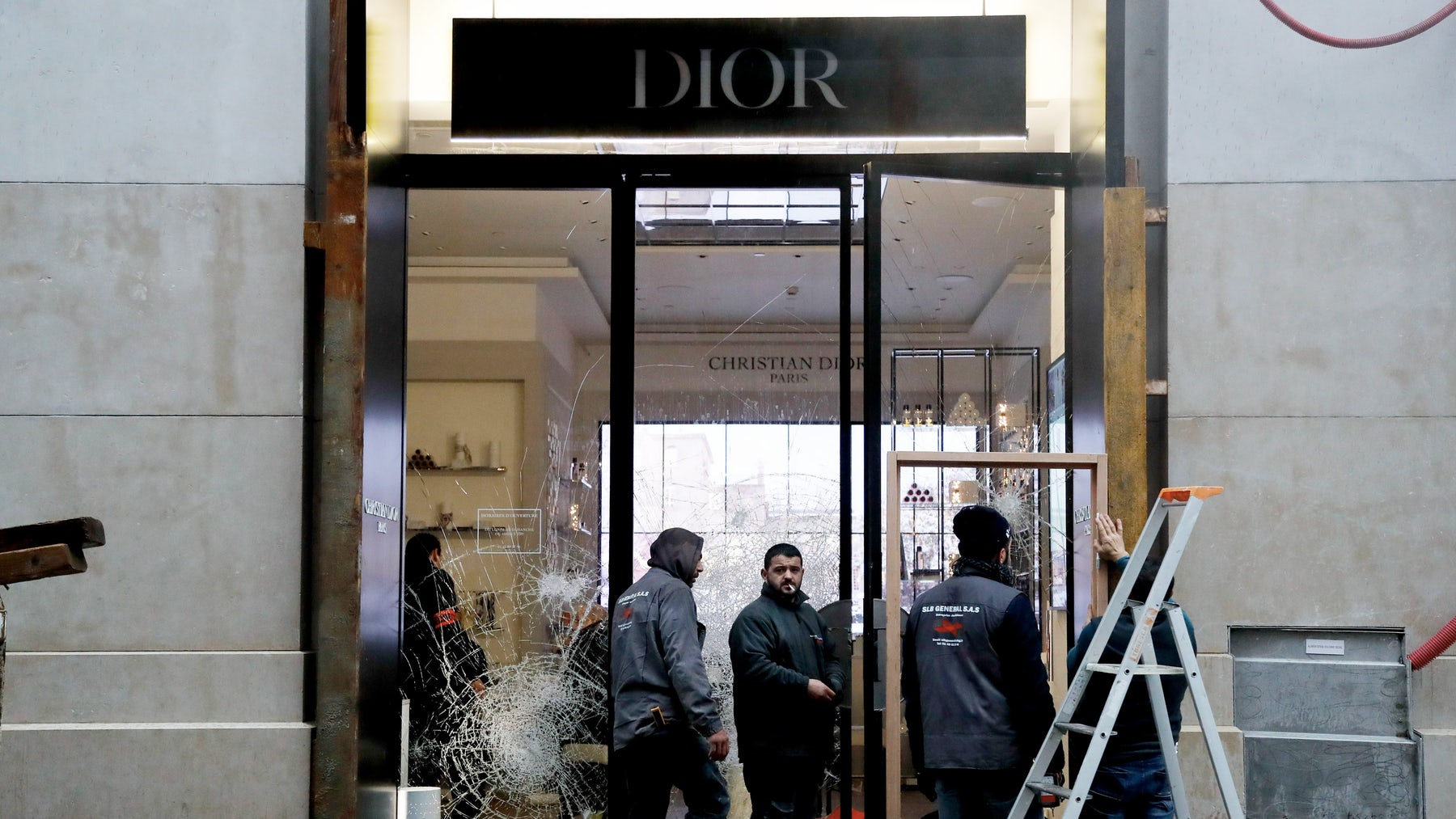 Workers repair the Dior shop window on the Champs-Elysees avenue in Paris after a rally by yellow vest protestors | Source: Getty Images