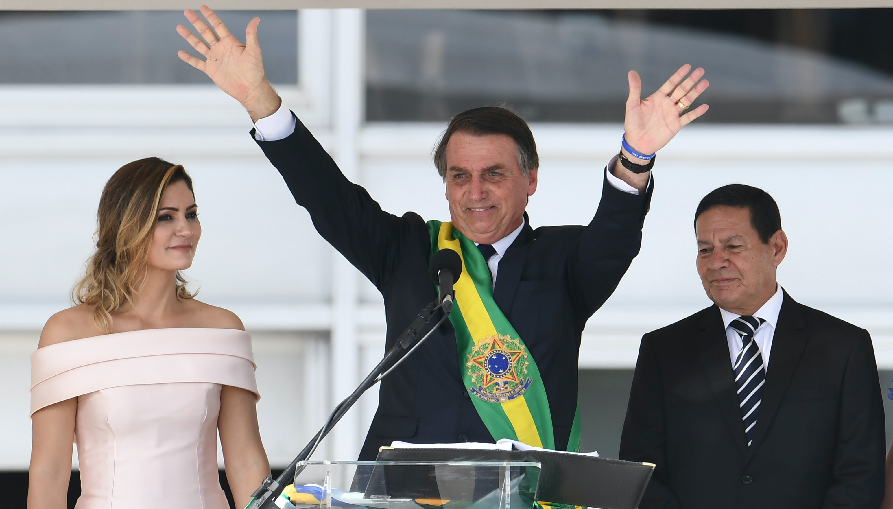 Jair Bolsonaro waves to supporters flanked by First Lady Michelle Bolsonaro (L) and Brazil's new Vice-President Hamilton Mourao, during their inauguration ceremony | Source: Getty Images)
